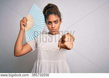 Young african american girl using hand fan to refreshment over isolated white background pointing with finger to the camera and to you, hand sign, positive and confident gesture from the front