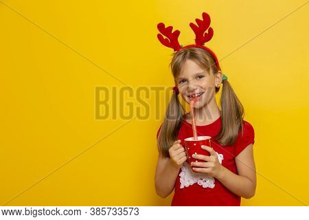 Portrait Of Beautiful Little Girl Wearing Deer Antlers Costume, Holding A Red Cup And Drinking Juice