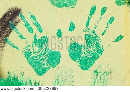 Green Handprints On The Metal Brown Surface.