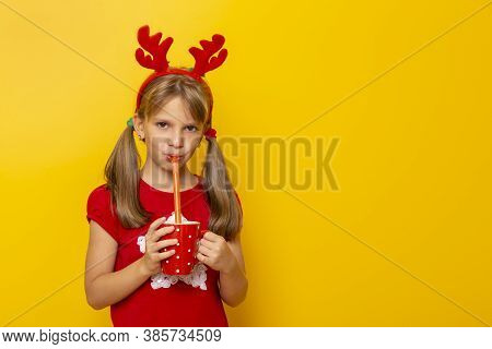 Child Wearing Deer Antlers Costume, Holding A Red Cup And Drinking Juice, Isolated On Yellow Colored