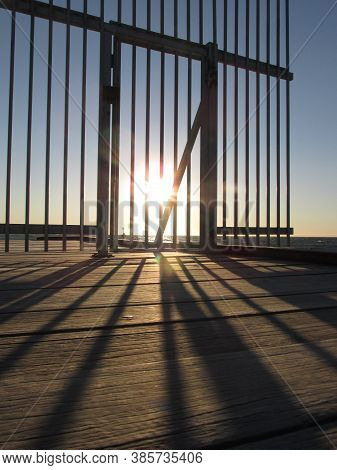 The Afternoon Sun Casts Shadows Of The Barrier Bars Of The Seaford Beach Jetty. The Barrier Is A Rec