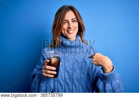 Young beautiful brunette woman drinking glass with  refreshment over blue background with surprise face pointing finger to herself