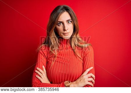 Young beautiful brunette woman wearing casual turtleneck sweater over red background skeptic and nervous, disapproving expression on face with crossed arms. Negative person.