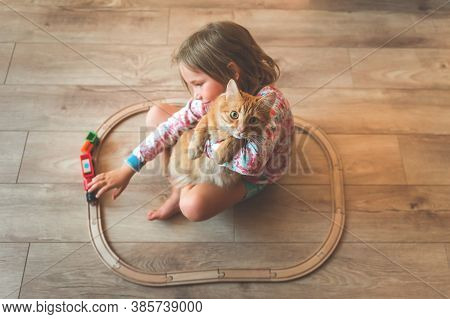 Happy Little Kid Play With Toy Wooden Train Railway At Home Together With Pet Cat. Toys For Children
