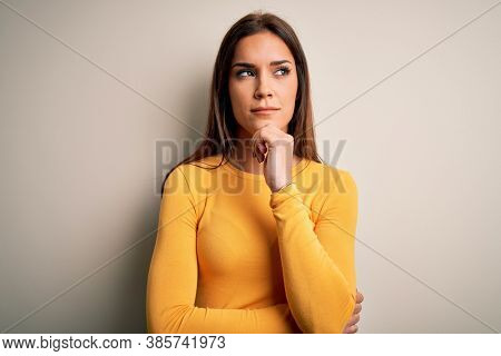 Young beautiful brunette woman wearing yellow casual t-shirt over white background with hand on chin thinking about question, pensive expression. Smiling with thoughtful face. Doubt concept.