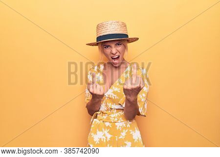 Beautiful blonde woman on vacation wearing summer hat and dress over yellow background Showing middle finger doing bad expression, provocation and rude attitude. Screaming excited