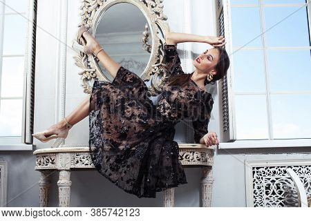 Young Pretty Lady In Black Lace Fashion Style Dress Posing In Rich Interior Of Royal Hotel Room With