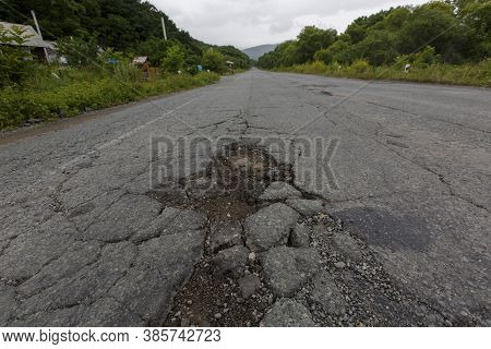 Very Bad Road In Russia. The Asphalt Road Is All In Holes In The Middle Of The Forest.
