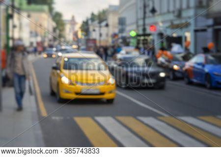 Defocused Blured View Of City Street Scene, Urban Traffic, Yellow Car Before The Pedestrian Crossing