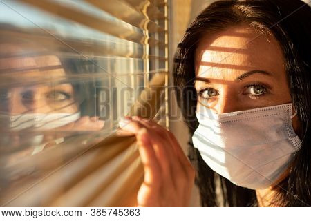 Woman with surgical mask looking out of home window, concept of quarantine during viral pandemic such as corona virus, sars or flu.