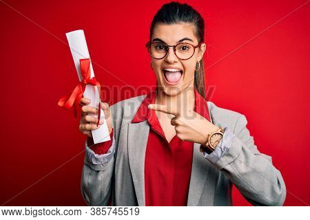 Young beautiful brunette student woman wearing glasses holding university degree diploma very happy pointing with hand and finger