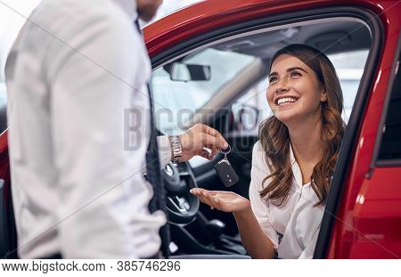 Crop Male Manager Giving Car Keys To Delighted Woman In New Car While Working In Dealership