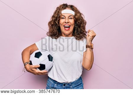 Middle age beautiful sporty woman playing soccer holding football bal over pink background screaming proud, celebrating victory and success very excited with raised arm