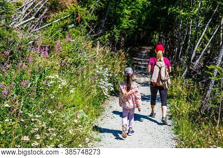 Mother With Daughter Hikers Trekking In Mountains.