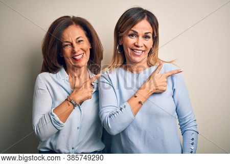 Middle age beautiful couple of sisters standing over isolated white background cheerful with a smile of face pointing with hand and finger up to the side with happy and natural expression on face