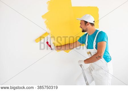 Side View Of Happy Young Male Painter In White Overall And Gloves Standing On Ladder And Painting Wa