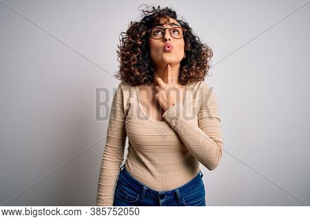Young beautiful curly arab woman wearing casual t-shirt and glasses over white background Thinking concentrated about doubt with finger on chin and looking up wondering