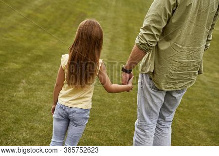 Back View Of A Little Girl Holding Hand Of Her Father While Spending Time Together Outdoors