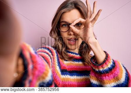 Young blonde girl wearing glasses taking a selfie picture of herself over pink isolated background with happy face smiling doing ok sign with hand on eye looking through fingers
