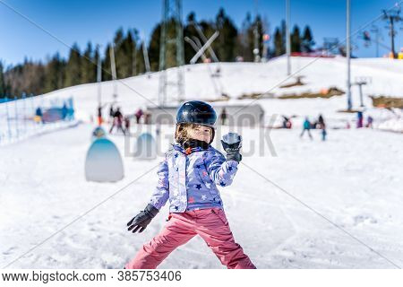 Young Happy Skier Girl Throwing Snowballs In Snowball Fight. Young Skier Having Fun On Ski Slope, Bi