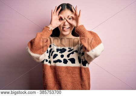 Young beautiful asian woman wearing animal print fashion sweater over pink isolated background doing ok gesture like binoculars sticking tongue out, eyes looking through fingers. Crazy expression.
