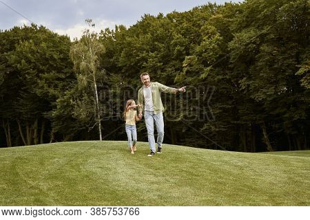 Spending Time With Dad. Young Father And His Cute Little Daughter Walking In The Park On A Warm Summ
