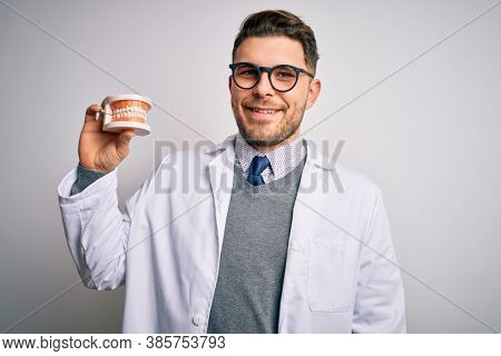 Young dentist man with blue eyes holding orthodontic dental prosthesis over isolated background with a happy face standing and smiling with a confident smile showing teeth