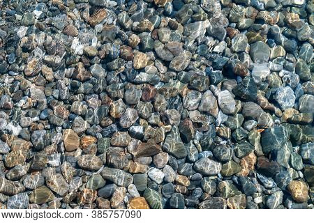 Texture Of Multicolored Pebbles In A Clear Shallow Sea Water
