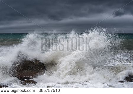 A Large Wave Breaks On A Rock During A Storm On The Black Sea In Crimea With A Dark Gloomy Sky