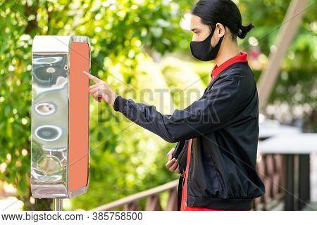 Asian delivery man using kiosk to ordering food and picking up this inline order to customer at fast food restaurant. Online technology self service new normal restaurant concept.