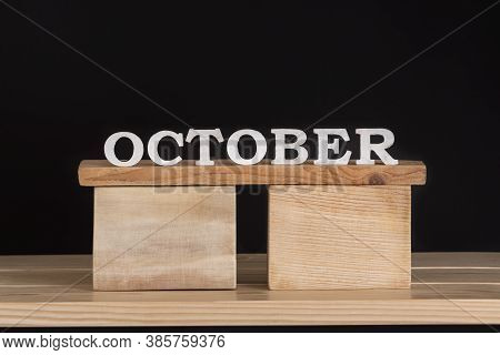 Word October By Wooden Letters On Black Background. Front View. Autumn Calendar. Fall Month.