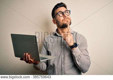 Young business man wearing glasses working using computer laptop serious face thinking about question, very confused idea