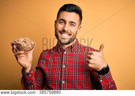 Young handsome man eating classic wholemeal cereals over yellow background happy with big smile doing ok sign, thumb up with fingers, excellent sign