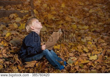 Little Boy Is Sitting In Wild Forest In Autumn Leaves With Book In Hands. Children's Books About Mir