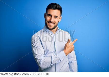 Young handsome man wearing elegant shirt standing over isolated blue background cheerful with a smile of face pointing with hand and finger up to the side with happy and natural expression on face