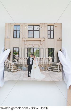 Hands In White Gloves Holding A Photo Book With Wedding Photos. Beautiful And Convenient Storage Of