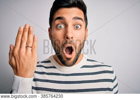 Handsome man with beard showing alliance ring marriage on finger over white background scared in shock with a surprise face, afraid and excited with fear expression