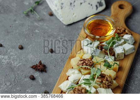 Close-up Of A Cheese Plate. 4 Types Of Cheese, Soft White Brie Cheese, Camembert, Semi-soft Briques,