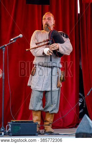 Russia. Vyborg. 08.20.2020. Man In Medieval Costume Playing Bagpipes At Summer Festival