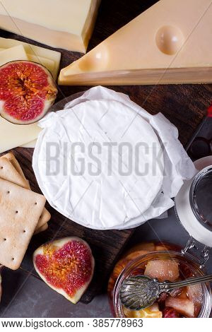 Brie Cheese And Other Types Of Cheese, Figs, Honey And Jam. Cheese Platter Served On The Wooden Boar