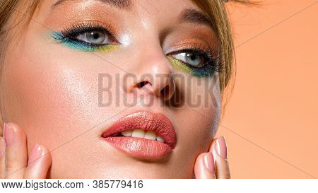 Beautiful woman with trandy makeup. Face of an young  woman close-up with a green color makeup. Stylish makeup.