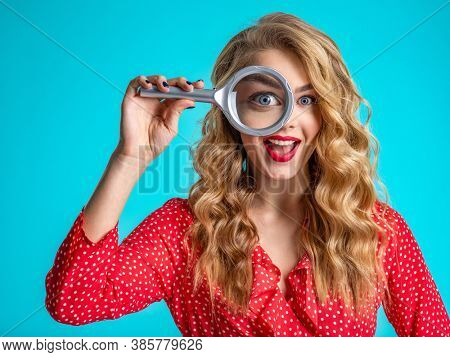 Cheerful blonde holds a magnifying glass in front eye. Young woman holds a magnifying glass in front of her eye. Funny  woman with a smile and loupe.