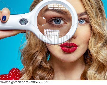 Blonde holds a magnifying glass in front eye. Young woman holds a magnifying glass in front of her eye. Funny woman  with a bright smile and loupe. Funny  woman . Eyesight care.