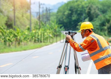Engineer Working With Theodolite Transit Equipment At Road.