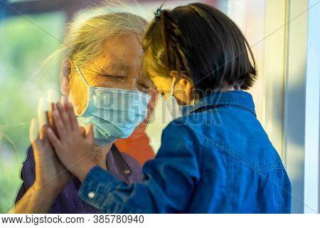 Hand Of The Grandma And Grandchild On A Window Plane,protection Coronavirus And Covid-19 Pandemic,so