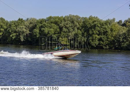 Modern Speedboat Sailing On Forest Background. Summer Leisure And Water Activity. Rest On The River