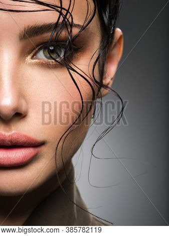 Closeup portrait of a beautiful young fashion woman with glamour makeup posing at studio. Smokey eye make-up. Face with a bang