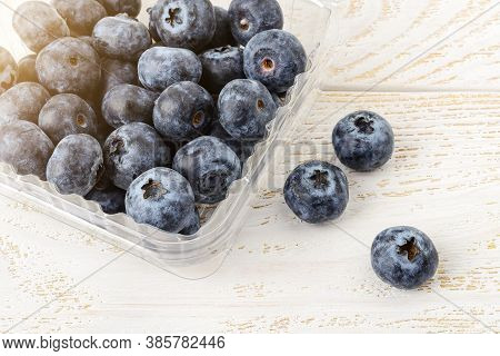 Fresh Organic Ripe Blueberries Or Vaccinium Myrtillus In A Disposable Food Container On A White Rust
