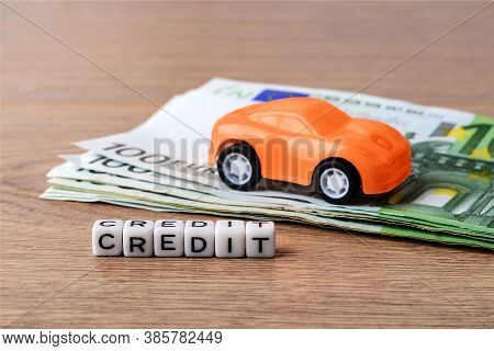 Orange Toy Car On Few 100 Euro Banknotes And Credit Word. Concept Of Car Buying, Renting, Service, R