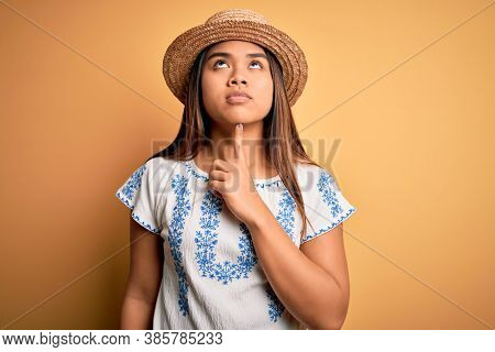 Young beautiful asian girl wearing casual t-shirt and hat standing over yellow background Thinking concentrated about doubt with finger on chin and looking up wondering